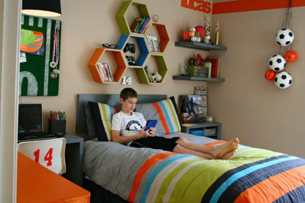 Age Boy Sitting In His Sports Themed Bedroom