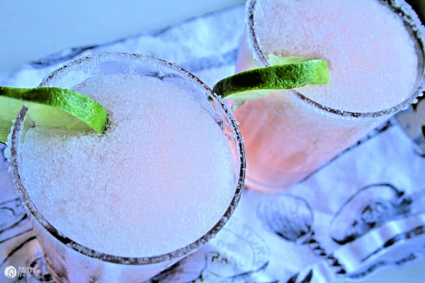 two glasses with pink margaritas with a lime