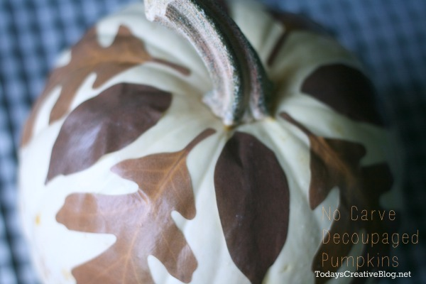 White pumpkin with leaves decoupaged to the top for fall decorating.