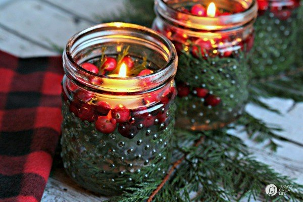 Jars filled with water, cedar and cranberries with a floating candle lit.