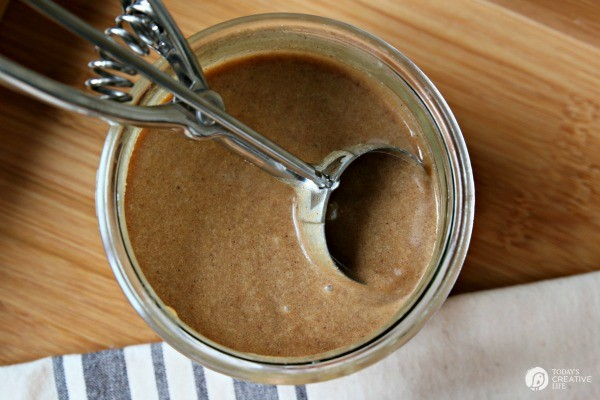 looking down into a jar of hot buttered rum mix with a small ice cream scooper inside.