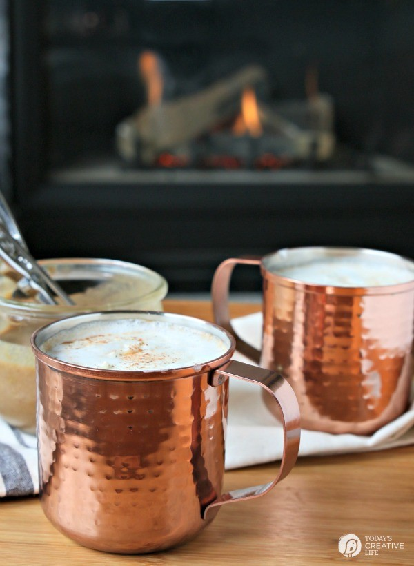 2 copper mugs filled with hot buttered rums next to a fire.