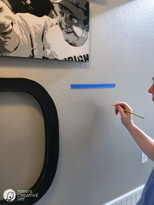 marking a wall for hanging photos