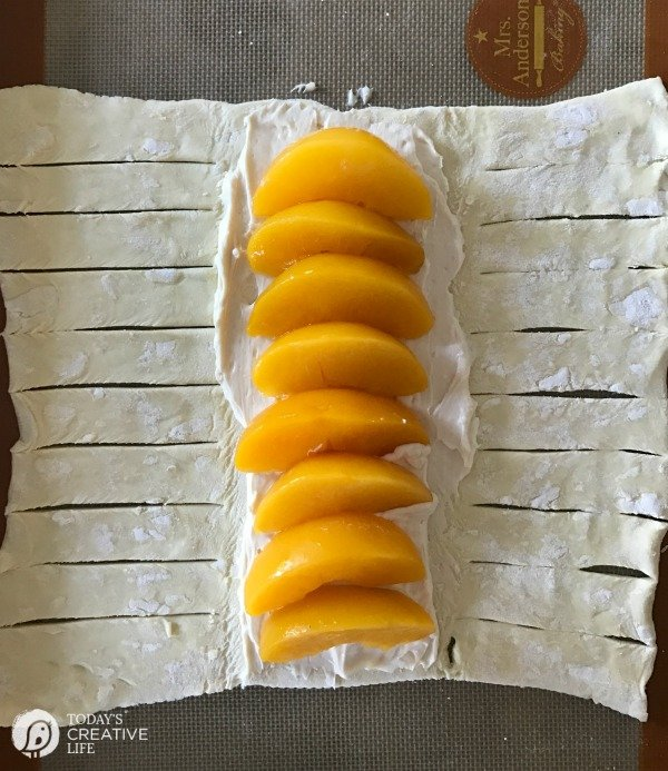 fresh peaches and sweetened cream cheese on a sheet of puff pastry
