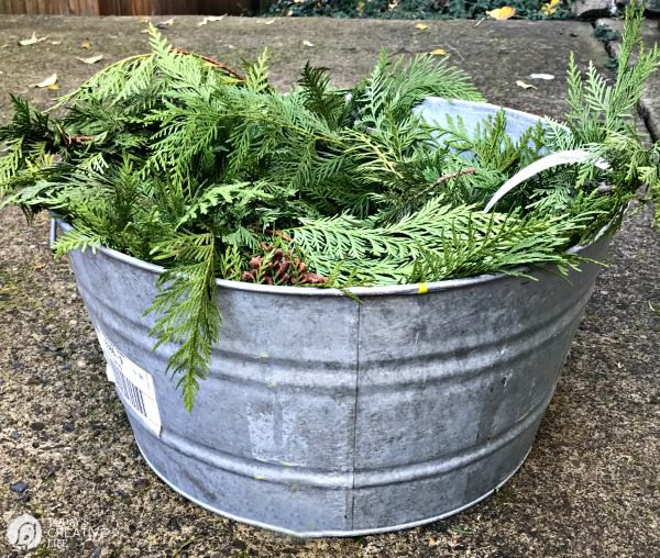 image shows how to keep garland fresh by soaking in a tub of water