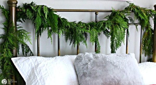 fresh garland hanging on a bedroom headboard