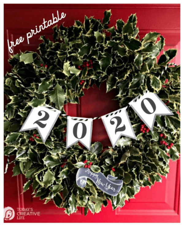 Holly wreath on red door with 2020 New years eve paper banner