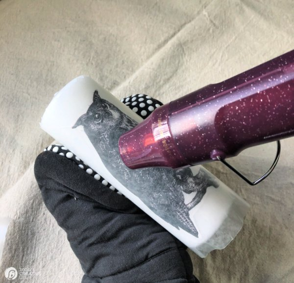 Hand in oven mitt using heat gun to blow hot air onto wax candle