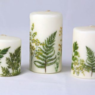 white candles with green ferns on them
