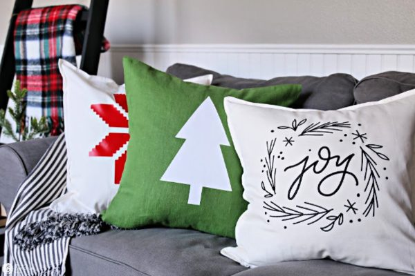 3 holiday themed pillows on sofa.