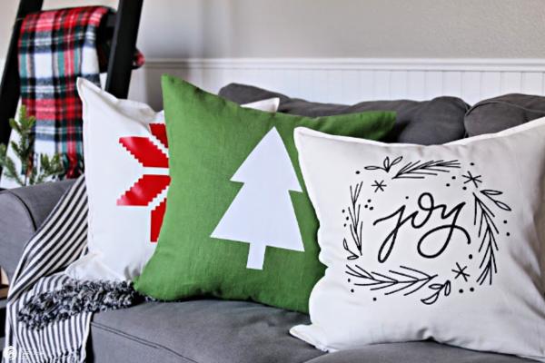 3 holiday themed pillows on sofa.