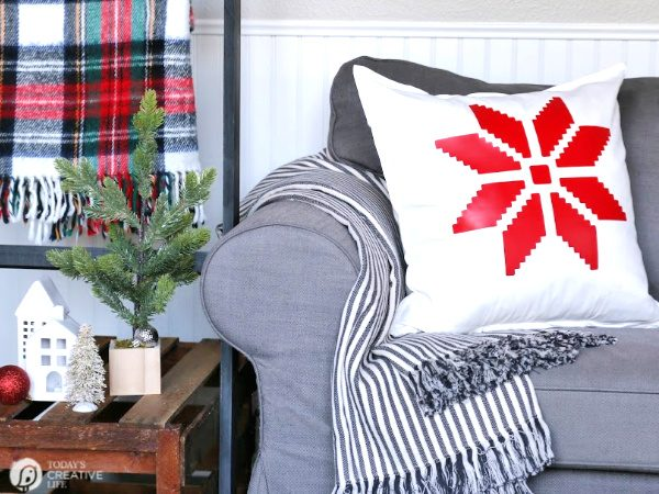 White pillow with Red Snowflake sitting on a grey sofa.