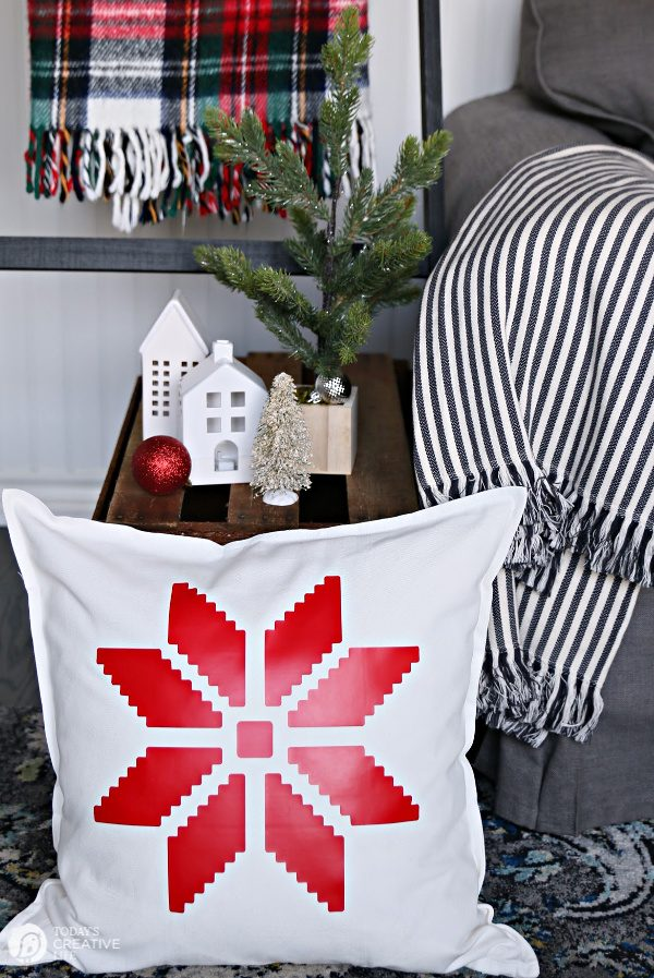 White Pillow with red snowflake sitting on the floor.