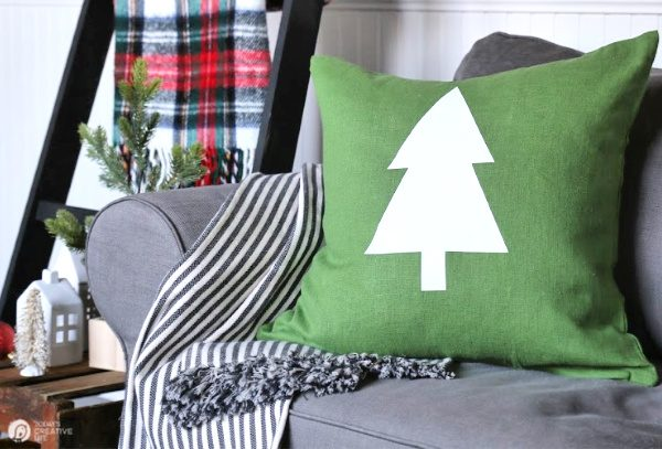 Holiday setting with green pillow with a white tree on it