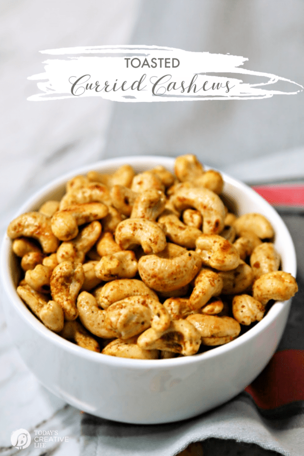 White bowl full of seasoned cashews.