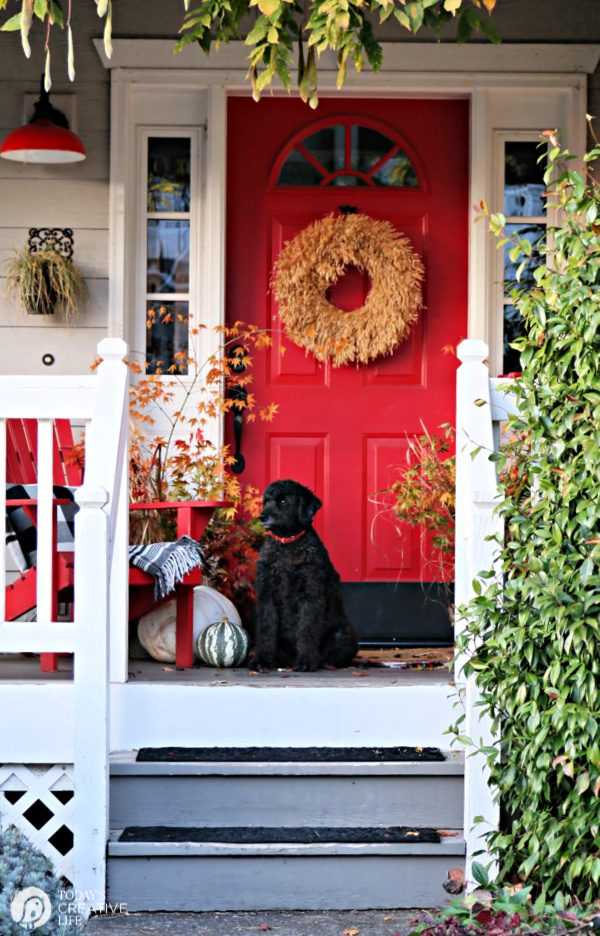 Porch with Red door decorated for Fall.