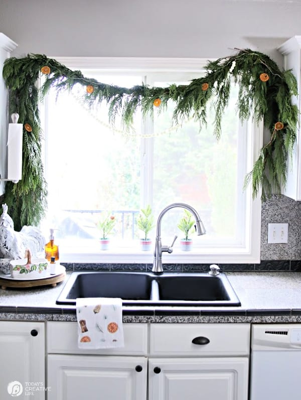 Cedar Garland with oranges over a kitchen sink window.