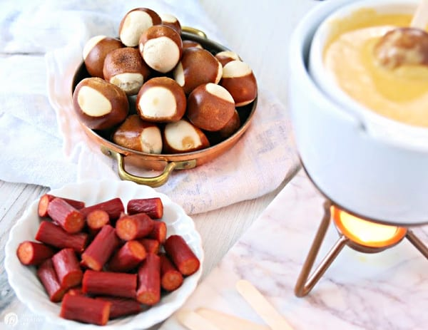Cheese fondue pot with plates of pretzel balls and pepperoni