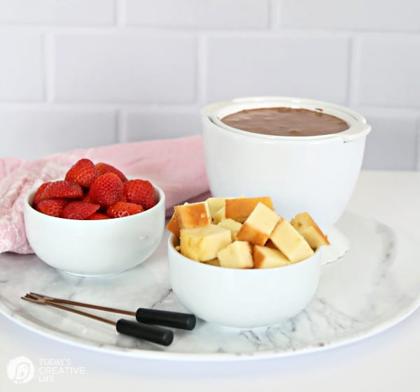 3 white bowls with chocolate fondue and dippers