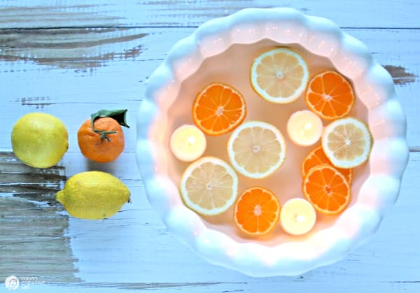 white bowl with floating sliced lemons and floating candles.