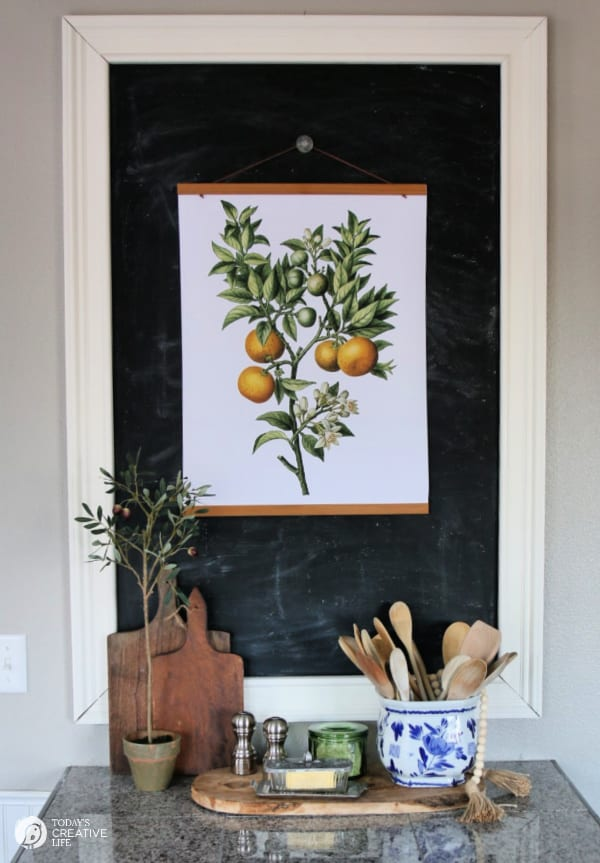 Large chalkboard with hanging botanical print of oranges.