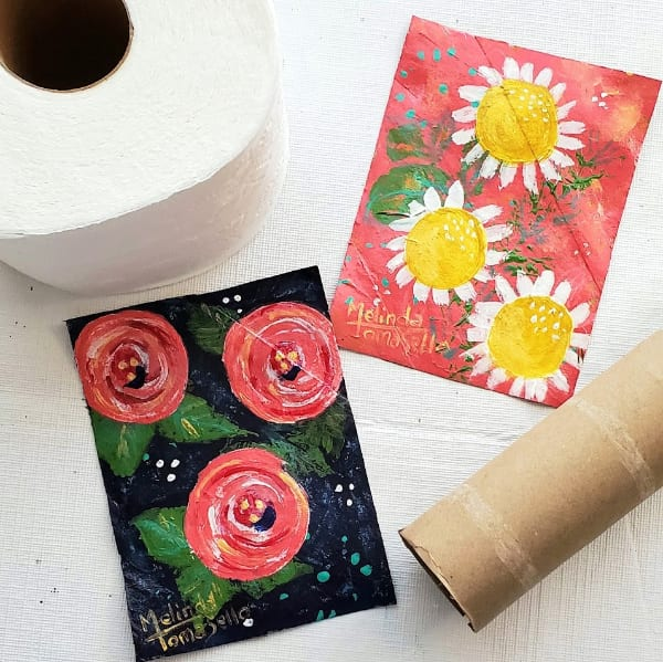 Flattened cardboard toilet paper rolls with painted art