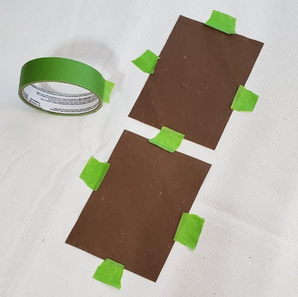 Taping down wet cardboard squares to dry