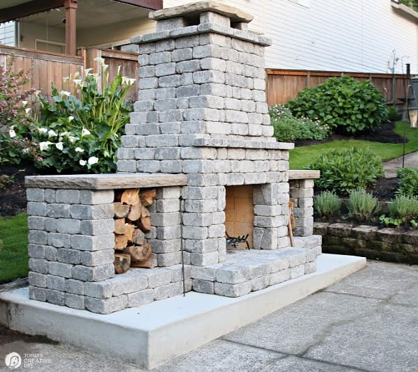 Grey stone backyard fireplace with wood boxes