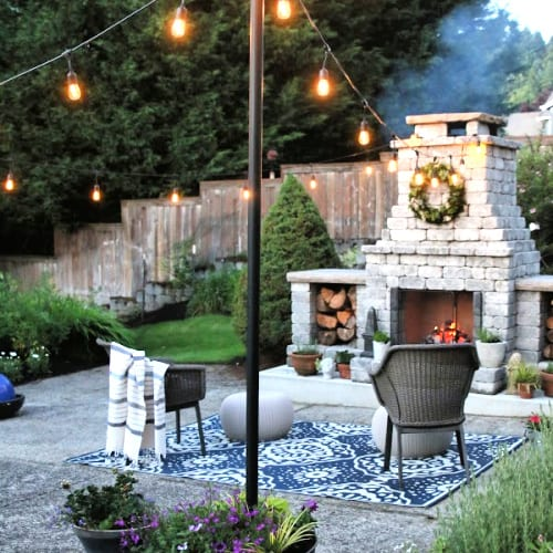 Outdoor hanging lights with outdoor fireplace.