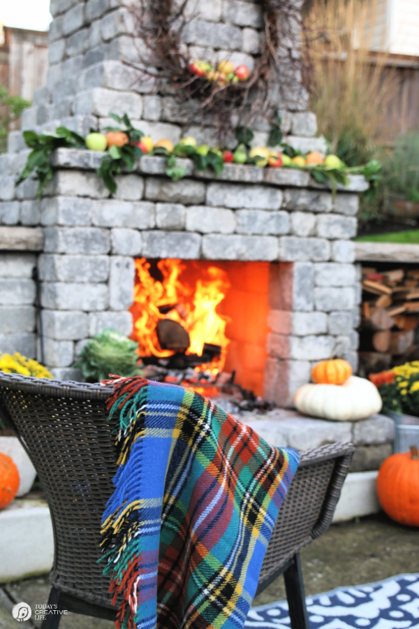 Outdoor Fall Decorating Ideas | outdoor fireplace with a roaring fire.