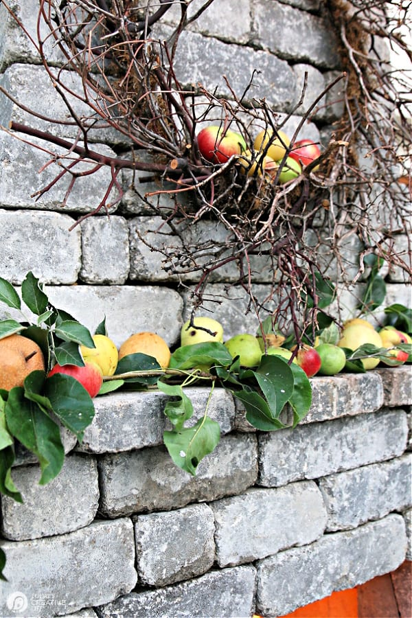 Outdoor fireplace with a twig wreath and apples on the mantel.