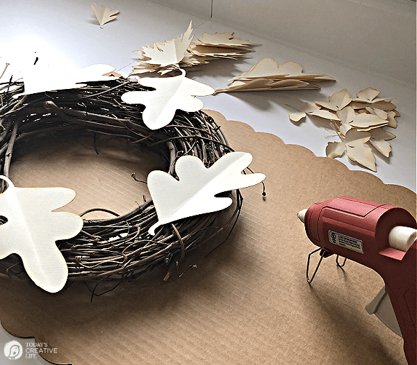 Gluing paper leaves to a grapevine wreath for a DIY Paper Leaf Wreath