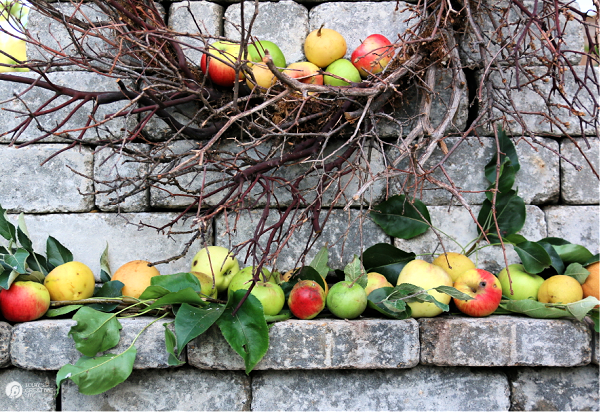 Apples and branches arranged on an outdoor fireplace mantel.