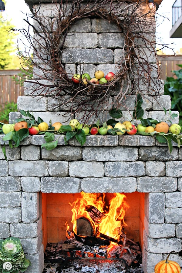Outdoor stone fireplace with apples on the mantle and a roaring fire.