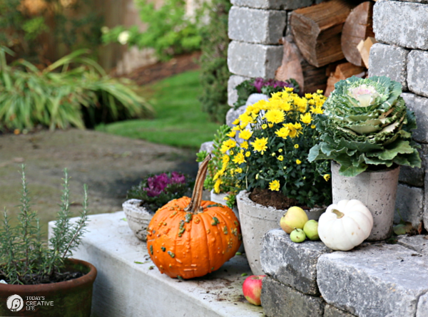 Decorating Ideas for Fall with pumpkins and mums on a fireplace hearth outside.