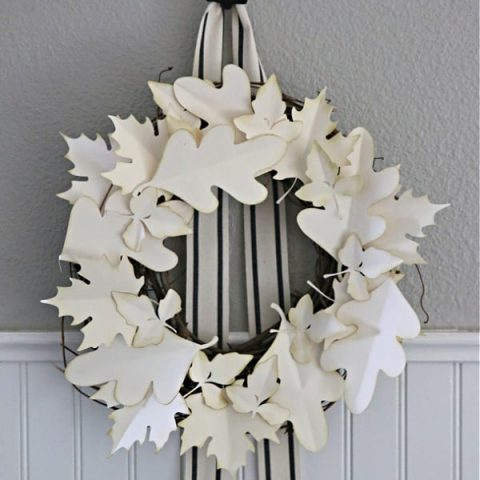 Fall Wreath made with cream colored paper leaves hanging on a wall.