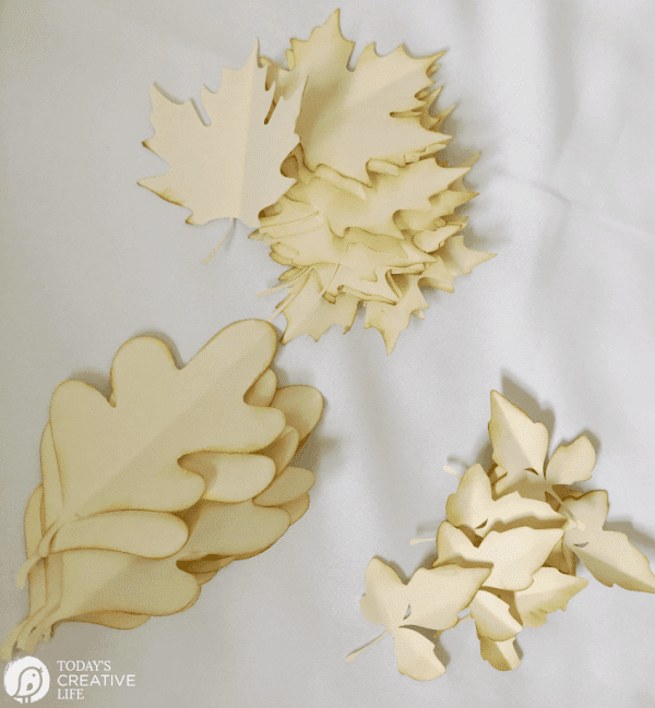 3 piles of cut paper leaves in 3 shapes
