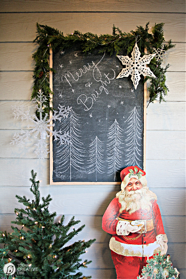 Christmas Porch Decorating Ideas with a vintage cut out of Santa and a holiday sign.