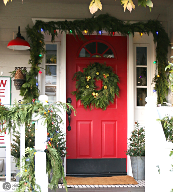 Front porch decorated for Christmas. Red Door with wreath.