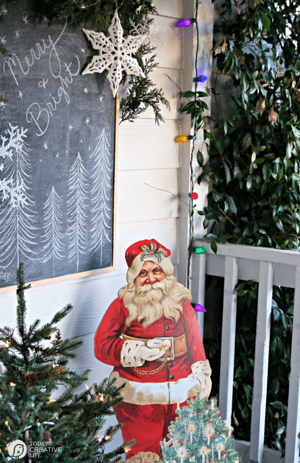 Christmas Porch Decorating Ideas with a vintage santa and small Christmas trees.
