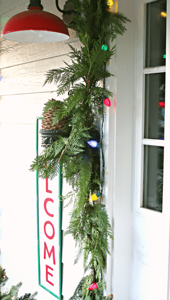 Green garland framing a door with holiday lights.