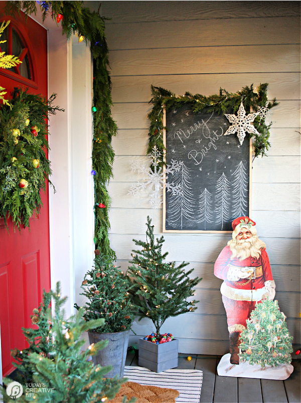 Christmas Porch Decorating Ideas with garland and a vintage Santa cutout.