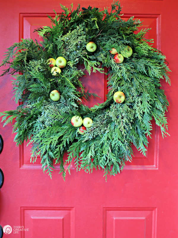Cedar wreath with apples on a red door.