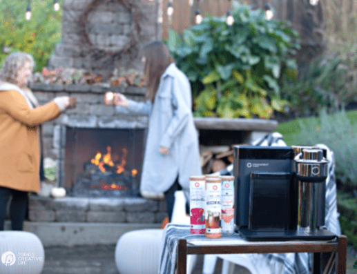 Drinkworks Home Bar with Two women standing next to outdoor fireplace