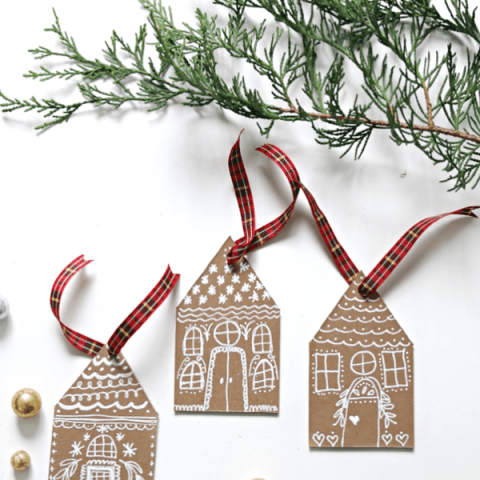 3 Gingerbread house DIY Christmas Ornaments made from chipboard or cardboard with white chalk marker drawings.