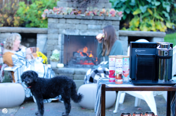 Outdoor setting with outdoor fireplace. 2 people chatting by the fire.