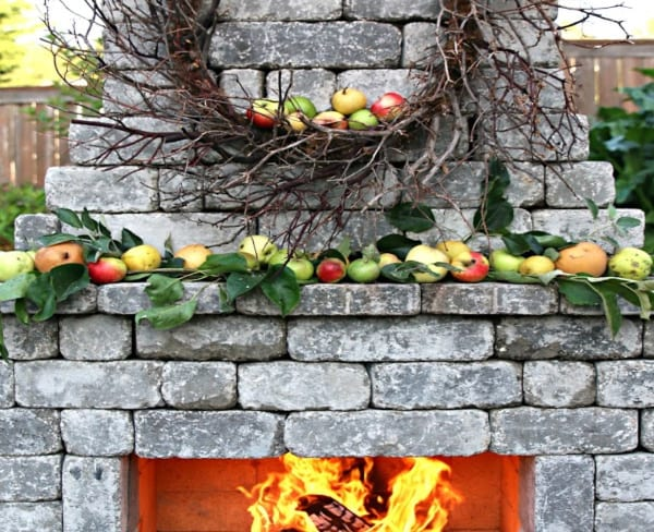 outdoor fireplace with decorated mantle for fall