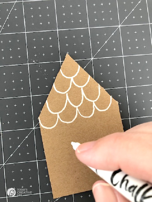 Drawing on a brown paper house with white chalk marker