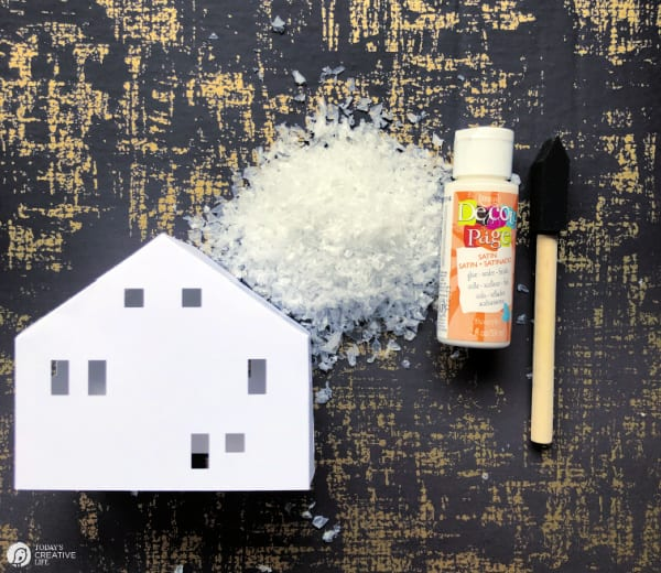 Paper house with a bottle of mod podge, a craft brush and faux snow.