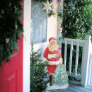 Vintage decorated Christmas Porch with garland and Santa cutout.